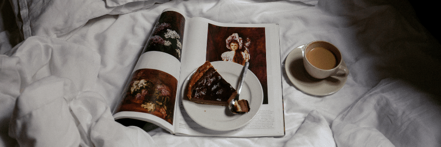 Coffee, sweets and books on bed